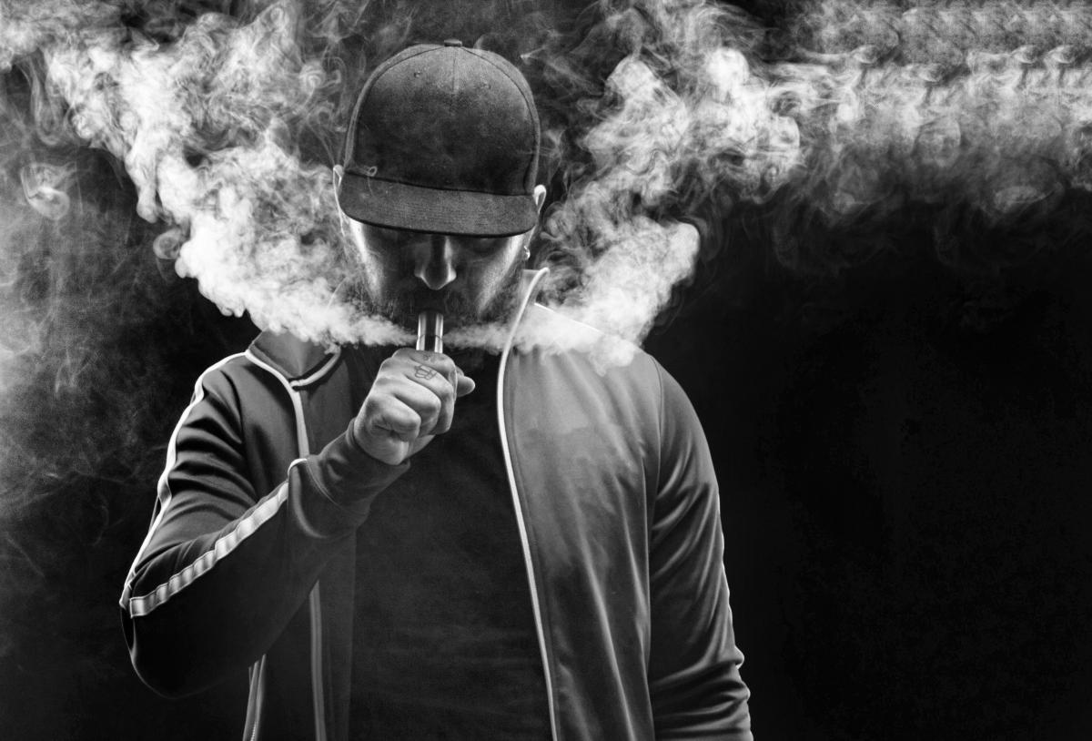 Black and white photo of young man using a vape pen