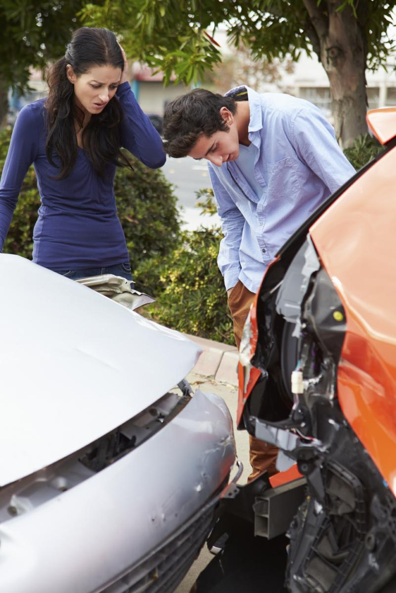 WOman and man looking at property damage following a car accident